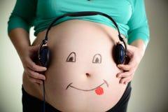 Le ventre enceinte écoute la musique par des écouteurs Images libres de droits