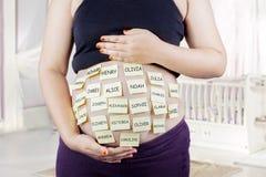 Le ventre enceinte avec le bébé appelle des choix Image libre de droits