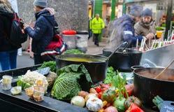 Le verdure accatastate su intorno al ghisa che cucina i vasi in pieno di cottura a vapore della minestra come clienti stanno into Fotografie Stock