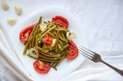 Le verdure al forno con la forcella d'argento su un piatto bianco hanno cucinato nel forno - il fagiolo, la patata, la cipolla, p Fotografia Stock