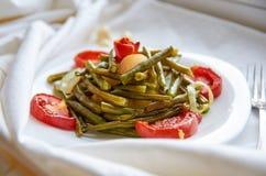 Le verdure al forno con la forcella d'argento su un piatto bianco hanno cucinato nel forno - il fagiolo, la patata, la cipolla, p Immagine Stock Libera da Diritti