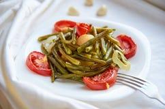 Le verdure al forno con la forcella d'argento su un piatto bianco hanno cucinato nel forno - il fagiolo, la patata, la cipolla, i Immagine Stock