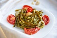 Le verdure al forno su un piatto bianco hanno cucinato nel forno - il fagiolo, la patata, la cipolla, pomodoro Su una superficie  Fotografie Stock