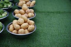 Le verdure delle patate fresche in ciotole ad un mercato si bloccano con il fondo dell'erba Fotografia Stock