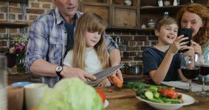 Le verdure di taglio di Help Daughter To del padre mentre il figlio e la madre usano Smart Phone delle cellule in cucina Parents  stock footage