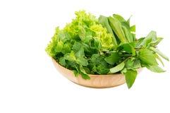 Le verdure verdi in piatto di legno su bianco hanno isolato il fondo Fotografia Stock