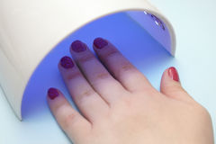 le vernis sur les clous, l'émetteur à rayonnement ultraviolet sèche la laque de gel Photos libres de droits