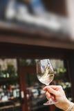 Le verre à vin avec du vin blanc à disposition, personne mélange la boisson d'alcool images stock