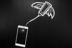 Le verre cassé du smartphone sur le fond noir et son âme vole loin sur le ciel écrit par la craie Images libres de droits