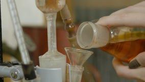 Le verre chimique avec le fluide vert a versé dans rouge parmi les entonnoirs La main ajoute le liquide mélangé rouge dans le fla Photo stock