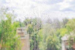 Le verre dans les gouttes de pluie La vue de la fenêtre de la ville Jour pluvieux Photo stock