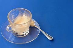 Le verre de café est alors employé sur un fond bleu Images stock
