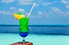 Le verre de la boisson est sur une table de plage Images libres de droits