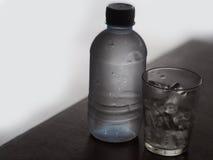 Le verre de la roche glace et bouteille d'eau Photo libre de droits