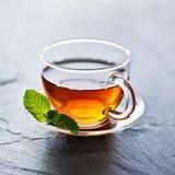 Le verre de thé chaud avec la menthe garnissent Image stock