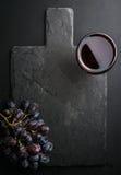 Le verre de vin rouge et les raisins sur la pierre noire d'ardoise embarquent au-dessus du fond foncé photos stock