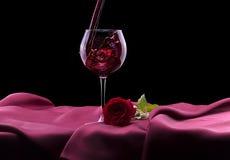 Le verre de vin rouge et s'est levé sur le noir Images libres de droits