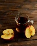 Le verre de vinaigre de cidre de pomme et deux moitiés d'une pomme Images stock