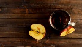 Le verre de vinaigre de cidre de pomme et deux moitiés d'une pomme Image stock