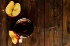 Le verre de vinaigre de cidre de pomme et deux moitiés d'une pomme Photos libres de droits