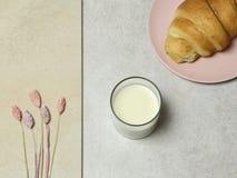 Le verre du lait, du gâteau et du bouquet des fleurs sur la texture de granit image libre de droits