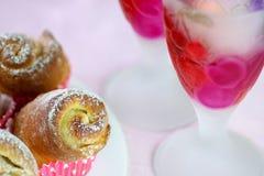 Le verre et les roses colorés bourgeonne des gâteaux pendant des vacances Images libres de droits