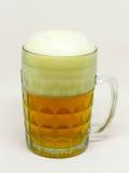 Le verre givré de bière blonde avec la mousse a placé sur un fond blanc Image stock