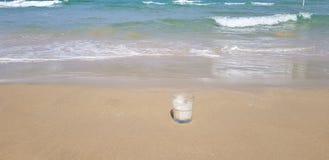 le verre transparent de caf? se tient en sable humide photographie stock libre de droits