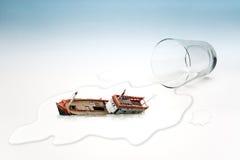 Le verre vide de l'eau avec le bateau a chaviré (le concept surréaliste) Photographie stock