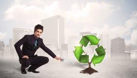 Le vert de arrosage d'homme d'affaires réutilisent l'arbre de signe sur le fond de ville Photos stock