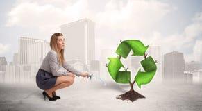 Le vert de arrosage de femme d'affaires réutilisent l'arbre de signe sur le backgrou de ville Image libre de droits