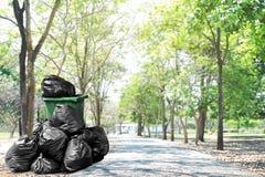 Le vert de poubelle de rebut réutilisent et les sachets en plastique de déchets à près de la route de manière de promenade, beauc photo libre de droits