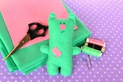 Le vert drôle a senti l'ours de nounours, jouet fait main d'enfants Ciseaux, fils, aiguilles - ensemble de couture Photos stock