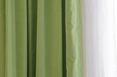 Le vert drape avec la lumière du soleil par les fenêtres Photos stock