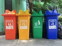 Le vert jaune et bleus rouges, réutilisent des poubelles avec réutilisent le symbole près de la construction extérieure Photos libres de droits