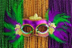 Le vert, l'or, et le Mardi Gras pourpre perle avec le masque Images stock