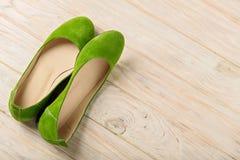 Le ` vert s de femmes chausse des ballerines sur le fond en bois Photographie stock