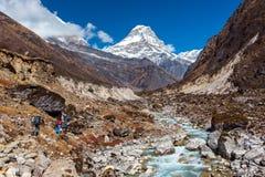 Le viandanti che camminano sulla traccia di montagna lungo il fiume scorrono Fotografie Stock Libere da Diritti