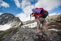 Le viandanti stanno scalando il pendio roccioso della montagna immagini stock libere da diritti
