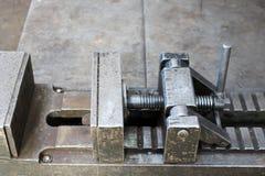 Le vice industriel lourd grand en métal avec un mécanisme de vis et les poignées, supports dans l'usine, la boutique est vue étro Photographie stock