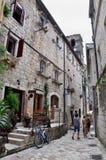 Le vie antiche di Cattaro, una bicicletta e la gente nel Montenegro Immagini Stock