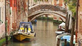 Le vie di Venezia, fiddle dell'uomo del lavoratore con le corde su una barca sul fiume fra le vie stock footage