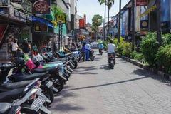 Le vie strette hanno allineato con i motobikes ed i turisti che passeggiano intorno ai negozi Immagine Stock