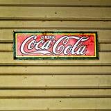 Le vieil acier de Coca-Cola de boissons se connectent le bâtiment jaune Photo libre de droits