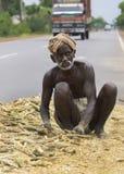Le vieil agriculteur à la peau foncée travaille son mellet sur la route publique Photographie stock libre de droits