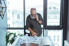Le vieil architecte habile a la conversation sur le smartphone Images libres de droits