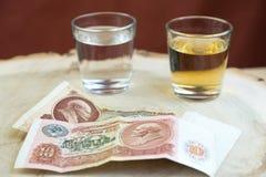 Le vieil argent de la Russie et deux verres avec de l'alcool sur un support de type tronçon en bois, le fond est rouge brouillé Photos libres de droits
