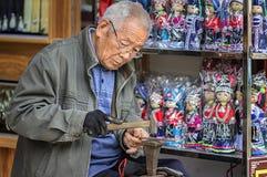 Le vieil artisan qui traite l'argenterie Image stock