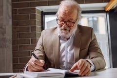 Le vieil auteur dans des vêtements intelligents construit le complot avec du roman Image libre de droits