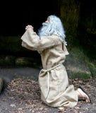 Le vieil ermite priant dans la caverne Images stock
